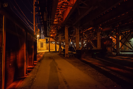Scary Chicago alley with a person's shadow under a vintage railroad bridge at night