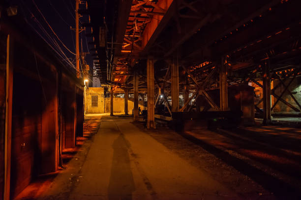 Scary Chicago alley with a person's shadow under a vintage railroad bridge at night stock photo