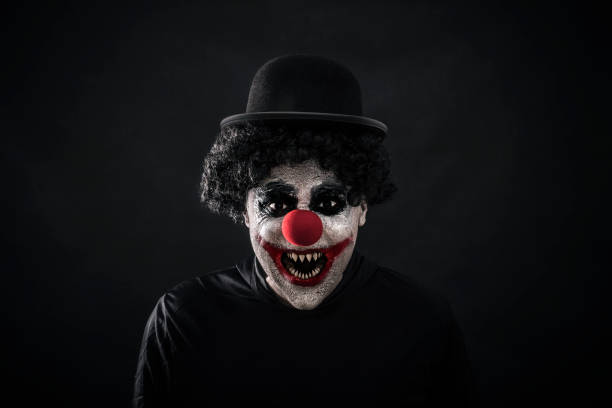Scary clown showing his sharp pointy teeth Scary clown showing his sharp pointy teeth fang stock pictures, royalty-free photos & images