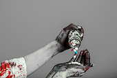 istock scary damaged girl in nurce halloween costume looking like zombie with pills on grey background 1056266104