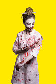 istock scary damaged girl in nurce halloween costume looking like zombie with syringe on yellow background 1056266164