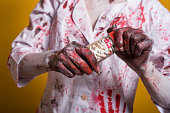 istock scary damaged girl in nurce halloween costume looking like zombie with pills on yellow background 1056274362