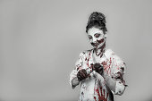 istock scary damaged girl in nurce halloween costume looking like zombie with pills on grey background 1056274376