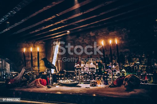 Spooky Halloween themed decoration with candles and skulls on nightclub bar counter for scary party