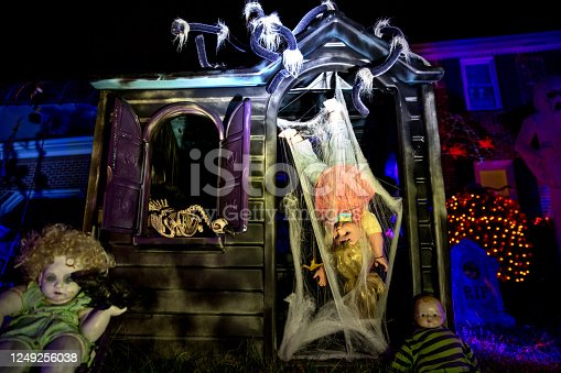 Nighttime view of a DIY haunted dollhouse amongst other spooky residential yard decorations