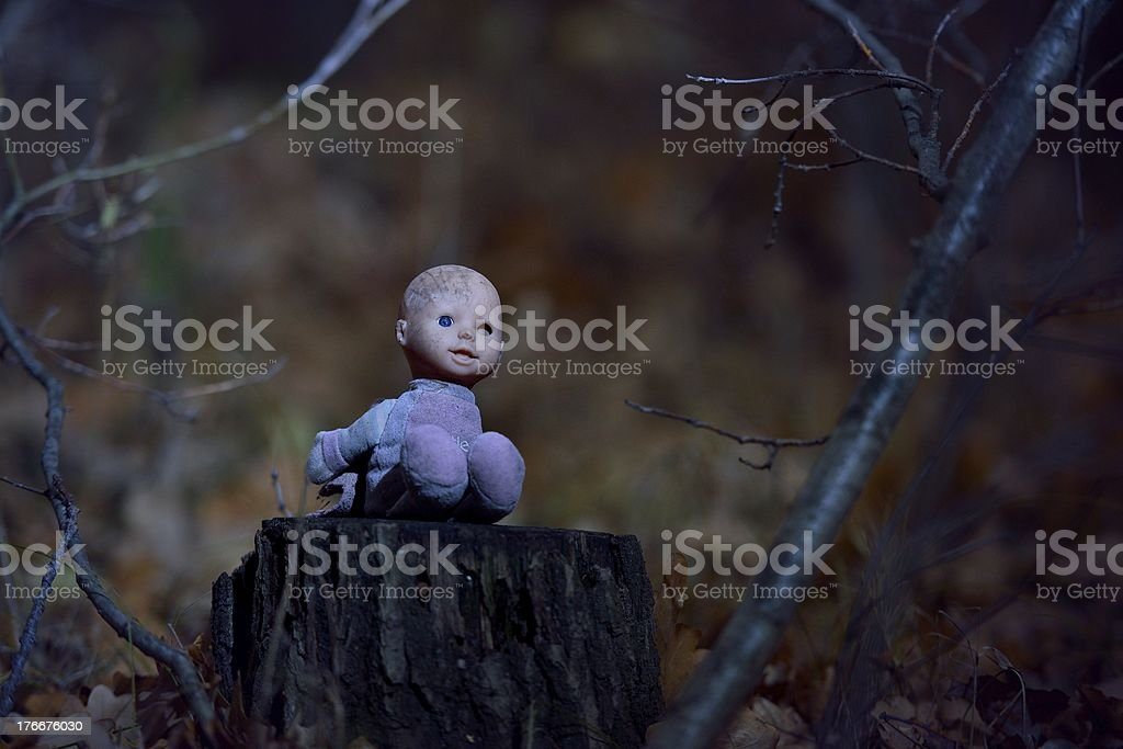 Scary doll on a stump in the night forest royalty-free stock photo