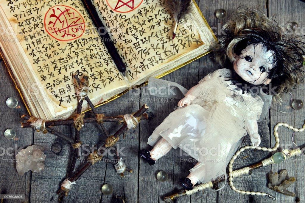 Doll miedo, pentagram y libro mágico abierto con símbolos mal en la tabla de la bruja - foto de stock