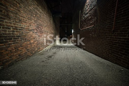 istock Scary empty dark alley with brick walls 904365946
