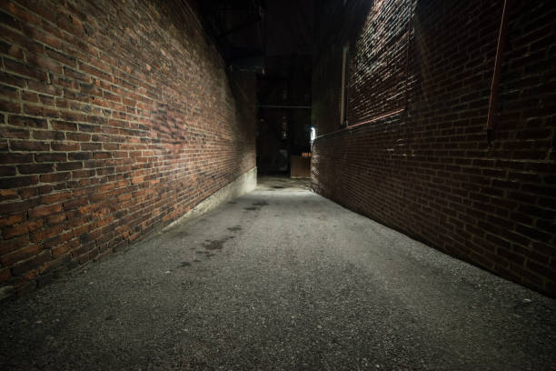 Scary empty dark alley with brick walls Scary empty dark alley with brick walls alley stock pictures, royalty-free photos & images