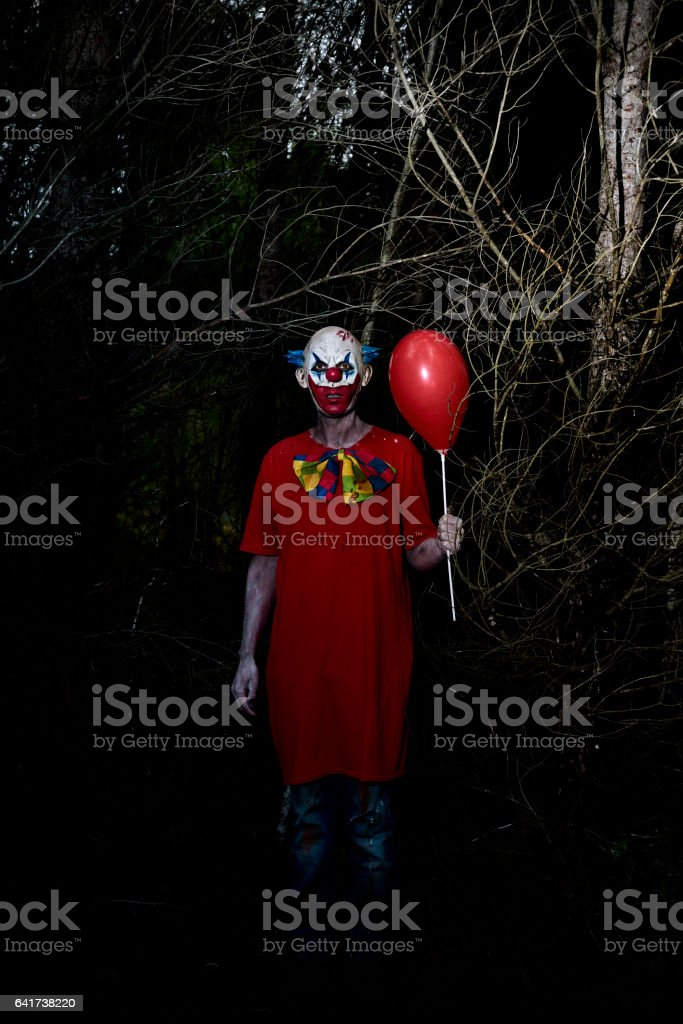 scary evil clown in the woods at night stock photo
