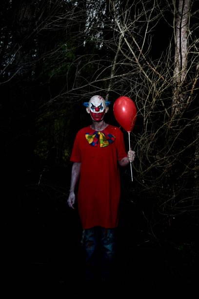 payaso mal siniestro en el bosque por la noche - foto de stock