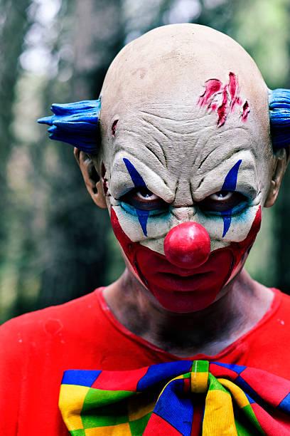 scary evil clown in the woods - horror zirkus stock-fotos und bilder