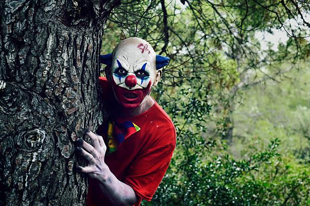scary evil clown in the woods - foto de stock