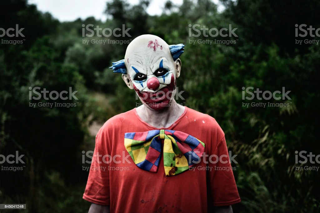 scary evil clown in the woods stock photo