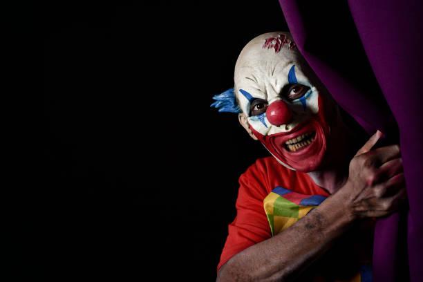 unheimlich böse clown peering aus einem bühnenvorhang - horror zirkus stock-fotos und bilder