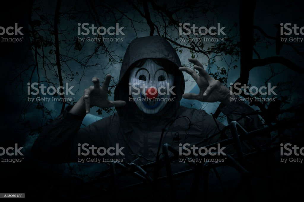 Scary evil clown wear jacket with old fence over dead tree, crow, moon and spooky cloudy sky stock photo