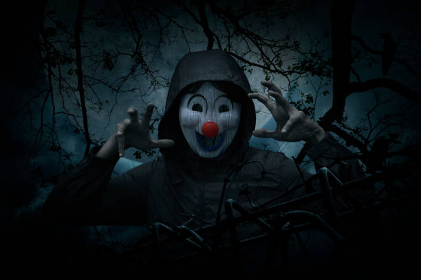scary evil clown wear jacket with old fence over dead tree, crow, moon and spooky cloudy sky - croak stock pictures, royalty-free photos & images
