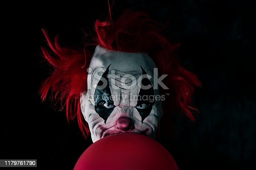 closeup of a scary evil clown with red hair and white eyes, staring at the observer, with a balloon in front of him, against a black background
