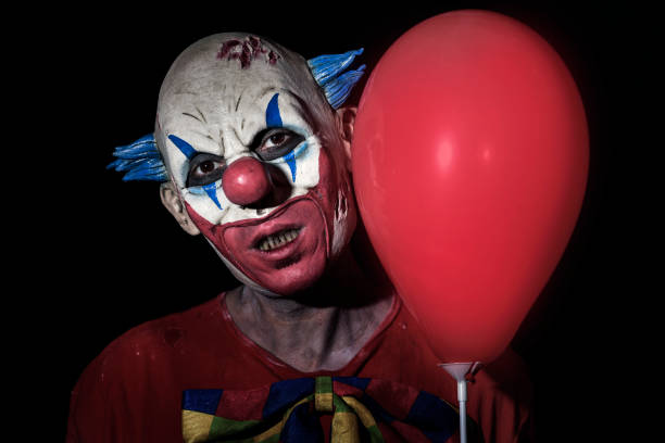 scary evil clown with a red balloon - killer stock photos and pictures