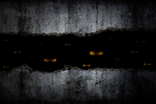 Scary eyes in damaged grungy crack and broken concrete wall and the dark