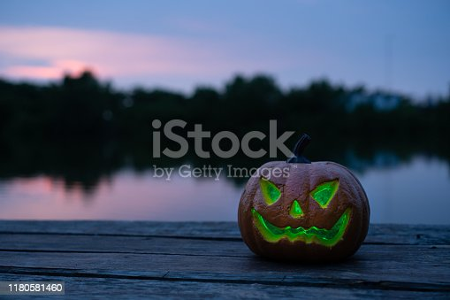 Scary face of jack-O'-lantern pumpkin by side of the lake. sunset time. for halloween background.