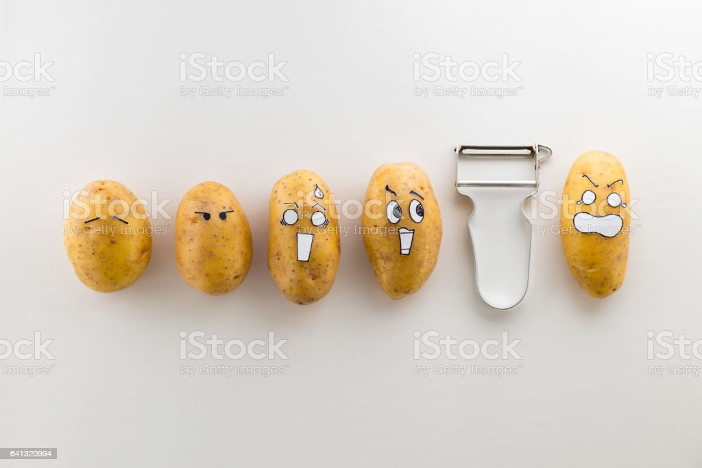 Scary face potatoes and peeler on white background stock photo