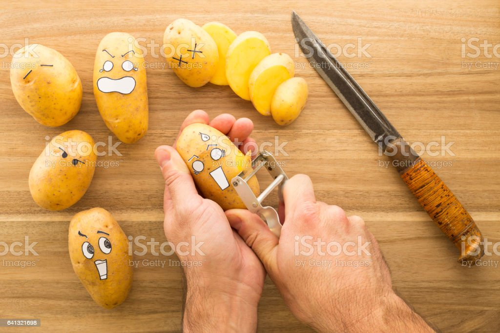Scary face potatoes being peeled on a wooden kitchen board stock photo