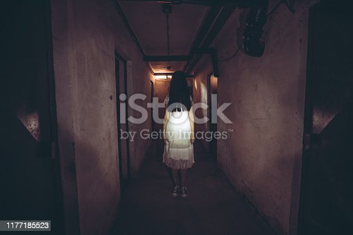 Scary ghost of a woman standing in dark basement corridor.