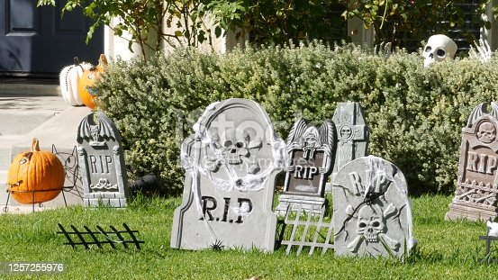 Scary festival decorations of a house, Happy Halloween holiday. Classic garden with Pumpkin, Bones and Skeleton. Traditional party decor. American culture.