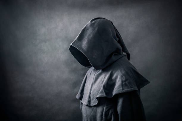 Scary figure in hooded cloak stock photo