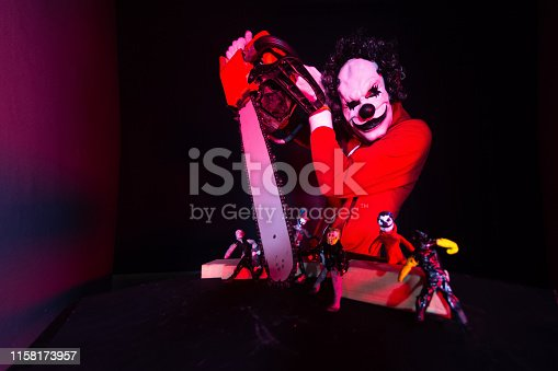 Scary halloween clown in red costume on black background. Killer clown holding a chainsaw