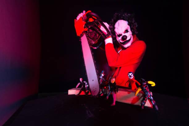 beängstigend halloween clown in rotem kostüm auf schwarzem hintergrund. killer-clown hält eine kettensäge - horror zirkus stock-fotos und bilder