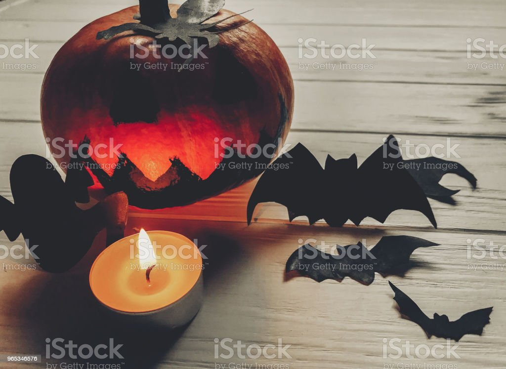 scary halloween. dark spooky jack lantern pumpkin with ghost bats and spider black decorations with candle light on wooden background. holiday celebration. seasonal greetings. happy halloween royalty-free stock photo