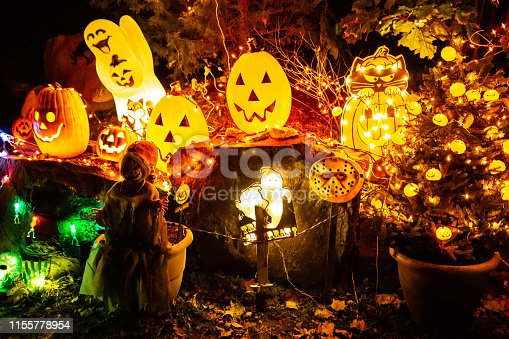 Scary Halloween decorations outdoors at night lighted