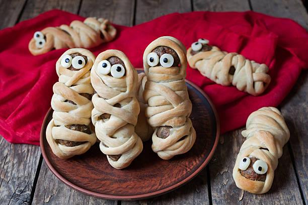 scary halloween essen fleischbällchen wurst mumien mit teig mit - halloween party lebensmittel stock-fotos und bilder