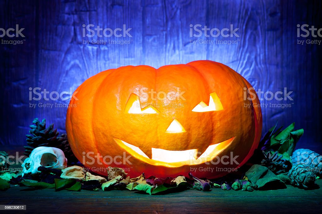 Scary Halloween pumpkin on a blue wooden background foto royalty-free