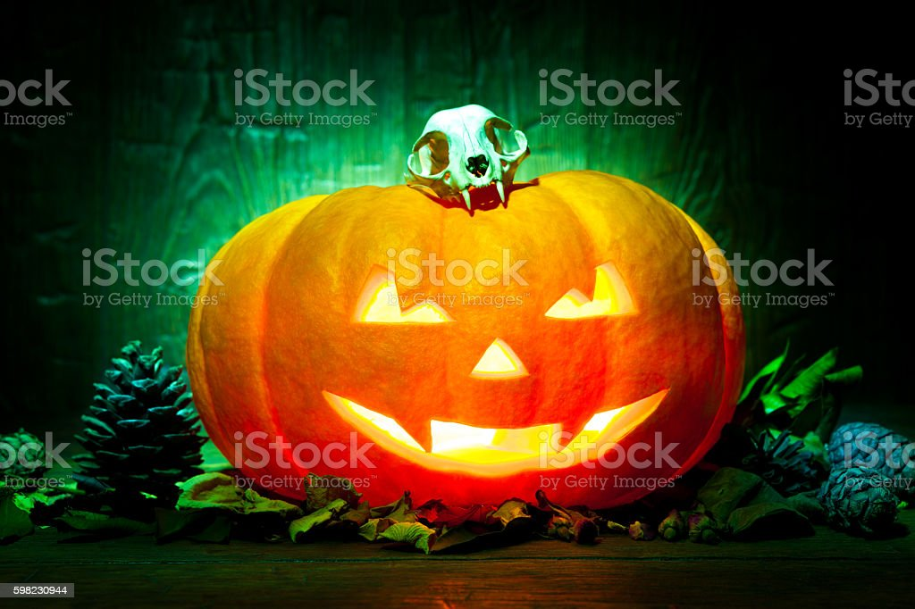 Scary Halloween pumpkin on a green wooden background foto royalty-free