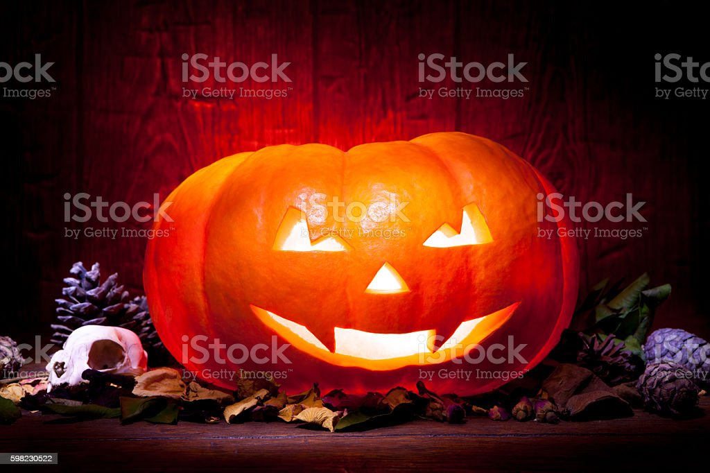 Scary Halloween pumpkin on a red wooden background foto royalty-free