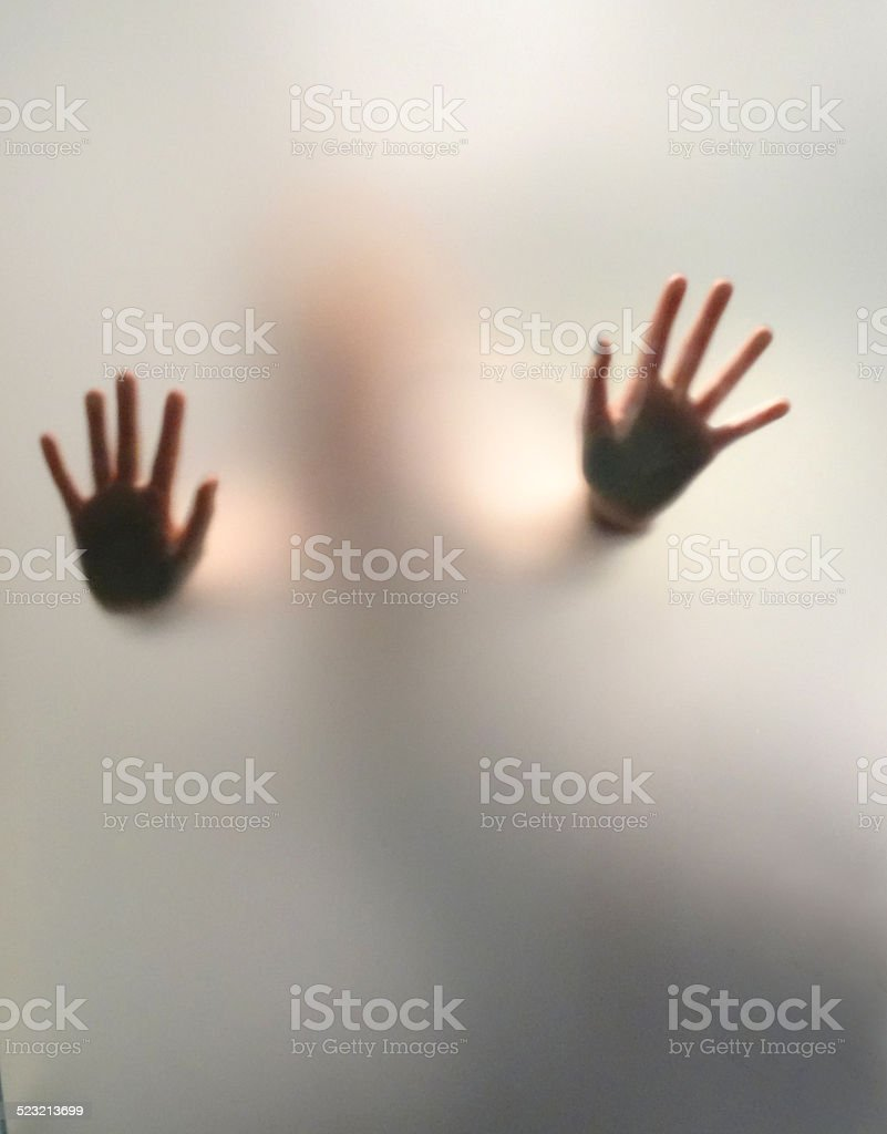 Scary hands silhouetted behind frosted steamed-up glass window / shower screen stock photo