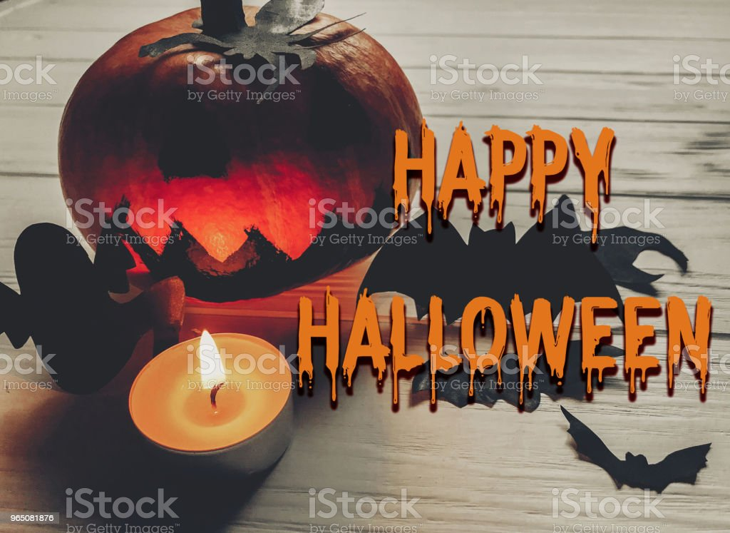scary happy halloween text. dark spooky jack lantern pumpkin with ghost bats and spider black decorations with candle light on wooden background. holiday celebration. seasonal greetings zbiór zdjęć royalty-free