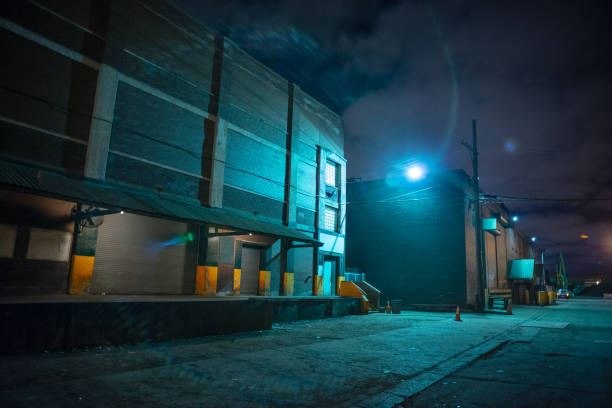 Scary industrial urban street city night scene with train loading docks by vintage factory warehouses stock photo