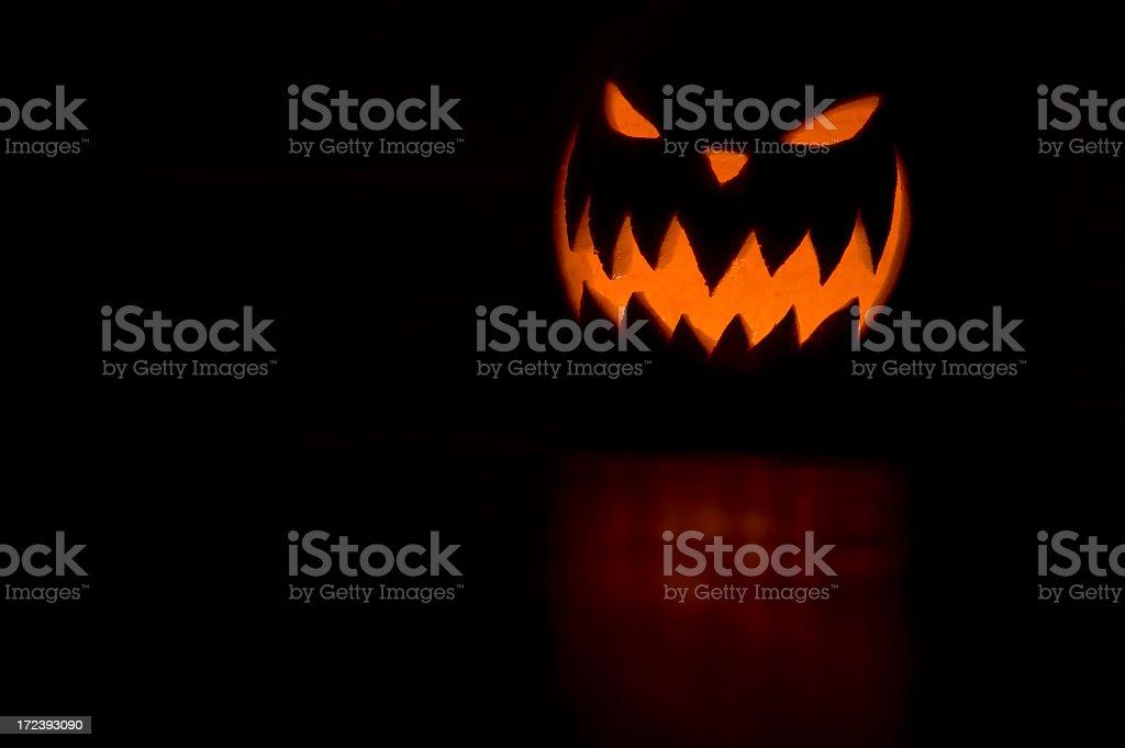 Scary Jack O Lantern on orange on black background royalty-free stock photo