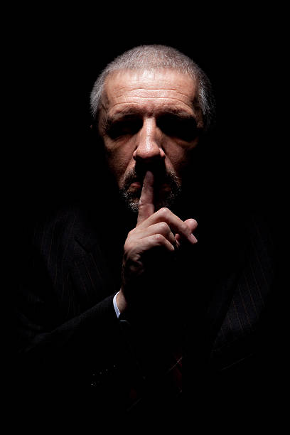 Scary man gesturing silence stock photo