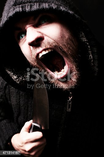 Scary screaming man brandishing a knife.