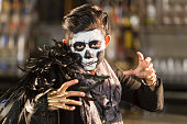A young Pacific Islander woman dressed as a scary monster, zombie or skeleton at an adult halloween party.