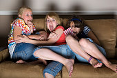 Three young girls huddled together on a couch watching a scary movie.  [url=search/lightbox/3091443] [img]http://richlegg.com/istock/banners/happy_children_banner.jpg[/img][/url] [b][url=search/lightbox/3091443]Click HERE to see my other HAPPY CHILDREN images[/url][/b]  [url=search/lightbox/11380995] [img]http://richlegg.com/istock/banners/eray_banner.jpg[/img][/url] [b][url=search/lightbox/11380995]Click here to see more of this model[/url][/b]  [url=search/lightbox/2239437] [img]http://richlegg.com/istock/banners/movies_banner.jpg[/img][/url] [b][url=search/lightbox/2239437]Click here to see more At The Movies images[/url][/b]