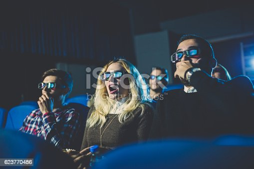 Friends watching a horror movie in a movie theater, getting scared and screaming.