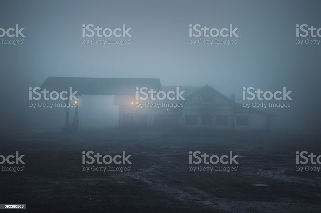 scary old gas station at night stock photo