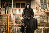 Scary man in black clothes sitting on fence in front of old house, man with shotgun is behind him