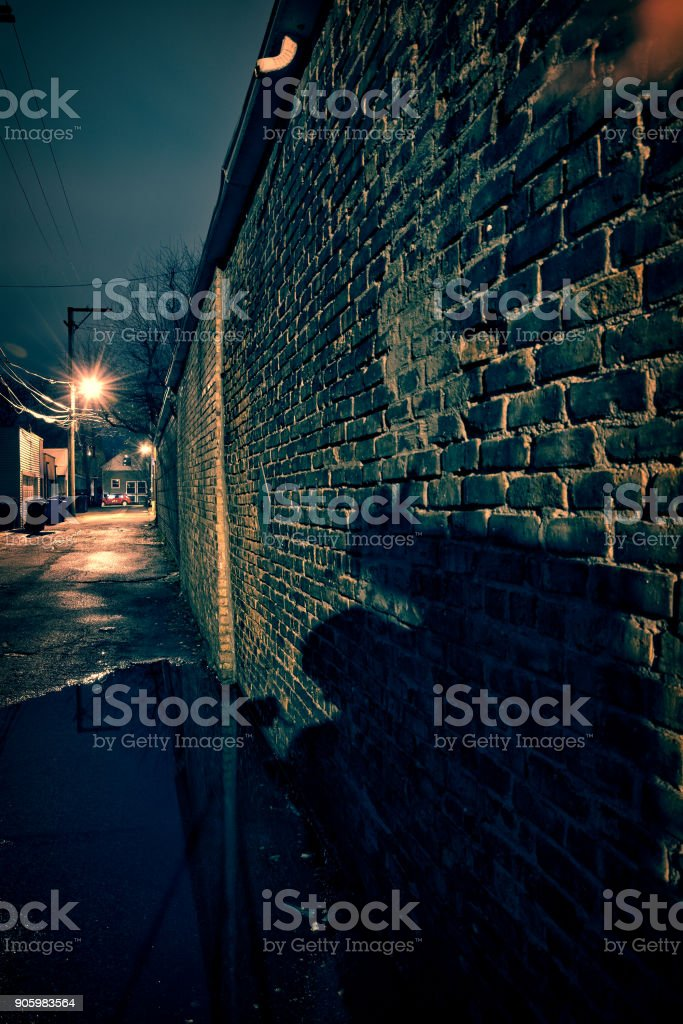Scary shadow on a vintage brick wall in a dark, gritty and wet Chicago alley at night after rain. stock photo